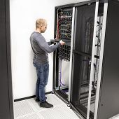 IT technician install network rack in datacenter