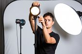 Young pro photographer in his studio setting up lights for the upcoming photoshoot (color toned image; shallow DOF)