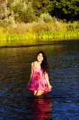 Smiling Asian American Woman Standing In River