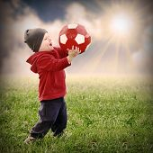 Little boy with soccer ball playing outdoor. Retro style picture.
