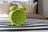 Modern Green Alarm Clock On Bed