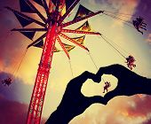 a silhouette of hands in the shape of a heart over a fair background toned with a retro vintage instagram filter effect