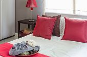 Red Pillow On Bed With Red Lamp On Table In Bedroom