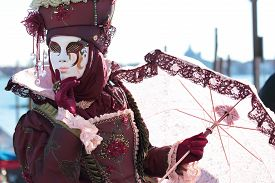 stock photo of venice carnival  - A red masked lady with parasol umbrella exhibited during the traditional festival of Carnival of Venice Italy  - JPG