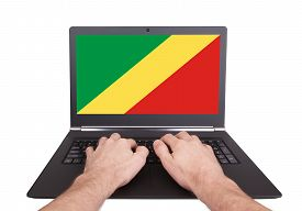 stock photo of congas  - Hands working on laptop showing on the screen the flag of Conga - JPG