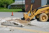 pic of backhoe  - a backhoe pulls up slabs of concrete from a roadway - JPG