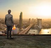 foto of land development  - engineering man standing on top of building looking to urban scene dreaming to new project - JPG
