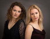 stock photo of shoulders  - Studio portrait of two woman friends shoulder to shoulder formally dressed looking in to the camera isolated against a dark grey background - JPG