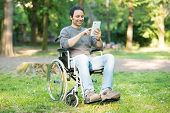 picture of wheelchair  - Detail of a man using a wheelchair in a park - JPG