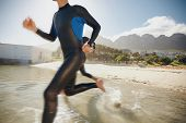 stock photo of triathlon  - Image of two triathletes rushing into the water - JPG