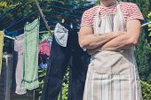 stock photo of clotheslines  - A young man wearing an apron is standing by a clothesline in the garden