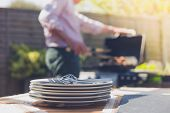 stock photo of braai  - Stack of plates on a table outside in a garden with a man attending to a barbecue in the background - JPG