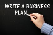 foto of writing  - Male hand wearing a business shirt writing the phrase Write A Business Plan on a blackboard in white text - JPG