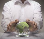 stock photo of environmental protection  - Image of a man in white shirt protect a glass earth with its hands - JPG