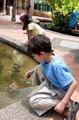 foto of catch fish  - Young boy enjoying a day catching and feeding fish in pond - JPG