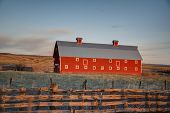 picture of red barn  - HDR colorful red barn in landscape at sunrise with fence and mountains in colorado - JPG