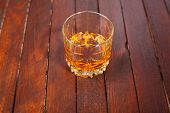 foto of tumblers  - Tumbler glass full of whisky standing on a wooden table - JPG