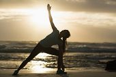 stock photo of stretch  - Sporty brunette stretching on the beach in the evening - JPG