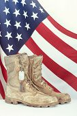 stock photo of boot  - Old combat boots and dog tags with American flag in the background - JPG