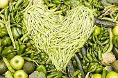 stock photo of green bean  - Heart made of green beans over green fruit and vegetable background - JPG