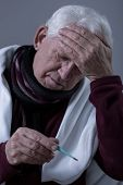 stock photo of high fever  - Older sick man with high fever and headache - JPG