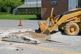 stock photo of backhoe  - a backhoe pulls up slabs of concrete from a roadway - JPG
