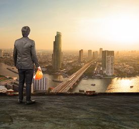 image of land development  - engineering man standing on top of building looking to urban scene dreaming to new project - JPG