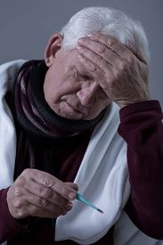 pic of high fever  - Older sick man with high fever and headache - JPG