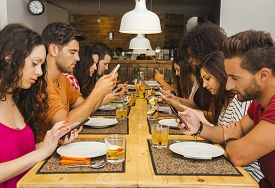 foto of table manners  - Group of friends at a restaurant with all people on the table occupied with cellphones - JPG