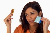 stock photo of condom use  - Young woman thinking about different contraceptive choices - JPG