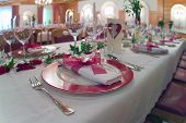 stock photo of wedding feast  - ceremonial decorated dinner table with pink plates - JPG