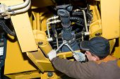 stock photo of wheel loader  - repairman worker screwing nuts of axle assembly in heavy wheel loader - JPG