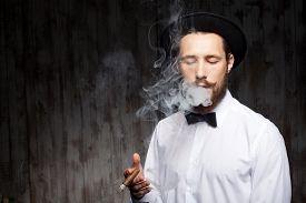 stock photo of smoke  - Cheerful hipster man is smoking cigar - JPG