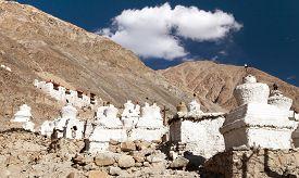 stock photo of karakoram  - Ruins of royal palace with white buddhist stupas in Tiger or Tiggur village in Nubra valley Ladakh Jammu and Kashmir India  - JPG