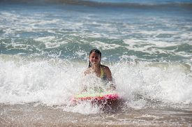 picture of boogie board  - Girl child getting splashed in face as she rides the boogie board - JPG