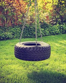 pic of tire swing  - an old rubber tire swing on chains in a backyard for kids to play on toned with a retro vintage instagram filter app or action effect  - JPG