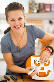 stock photo of carving  - Happy young woman in kitchen using stencils to carve scary pumpkin Jack - JPG