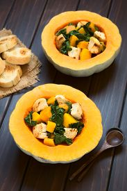 picture of half  - Pumpkin and chard salad with croutons served in pumpkin halves photographed on dark wood with natural light  - JPG