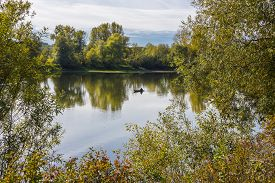 picture of novosibirsk  - Rustic fisherman sails on the boat on the fall river - JPG