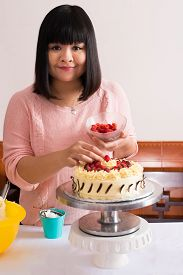 pic of pastry chef  - Vertical portrait of a young pastry chef decorating a homemade cake with fresh berries on the foreground - JPG