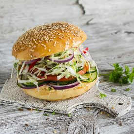 image of veggie burger  - delicious veggie burger with cabbage tomato cucumber onions and peppers on a light wooden surface - JPG