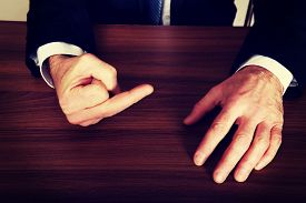 picture of middle finger  - Close up of businessman showing middle finger on the desk - JPG
