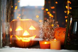 image of antichrist  - Halloween pumpkin and burning candles in window - JPG