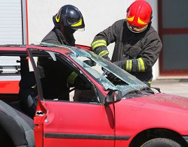 foto of firemen  - chief fireman whit red helmet while breaking the windshield of a car after road accident - JPG