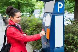 stock photo of insert  - Young Beautiful Woman Inserting Coin In Parking Meter - JPG