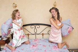 picture of pillow-fight  - Two beautiful young woman fighting with pillows in bed - JPG