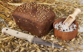 pic of salt shaker  - Loaf of homemade bread with black mustard seeds on a table with spikelets of rye and oat sand salt shaker salt and knife - JPG