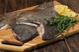 pic of flounder  - Fresh flounder prepared for cooking with lemon and thyme on a cutting board - JPG