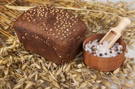 foto of salt shaker  - Loaf of homemade bread with black mustard seeds on a table with spikelets of rye and salt shaker of salt - JPG