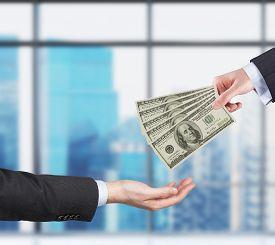 foto of two dollar bill  - Two hands money transferring process - JPG